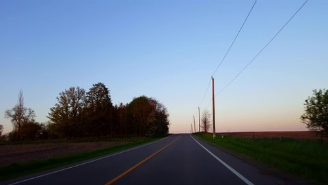 Driving Rural Countryside Road During Sunset.  Driver Point of View POV While Sun Rises on Horizon During Dusk Early Evening.