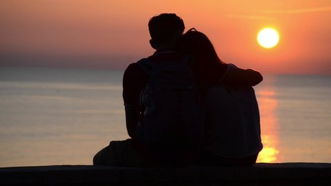 Young and romantic couple watching sun at golden and beautiful sunset on the beach. Silhouette of couple in love at sea. Boy and girl on holidays on romantic summer evening. Happy couple hugging