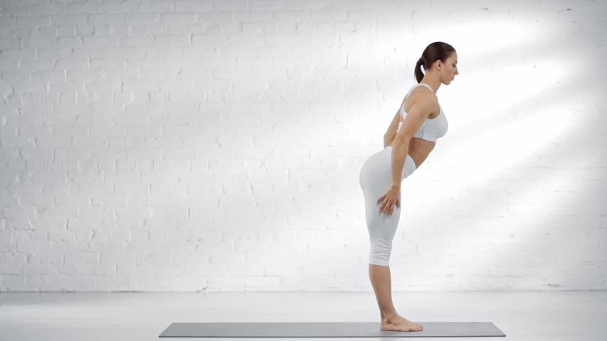 Side view of woman practicing uttanasana and adho mukha svanasana, raising leg, practicing eka pada adho mukha svanasana and eka pada koundinyasana   Shutterstock HD Video #1030328498