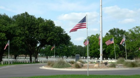 SAN ANTONIO, TX - MAY 27, 2019 - Fort Sam Houston National Cemetery during Memorial Day. Establishing shot tilting up with the focus on the american flag