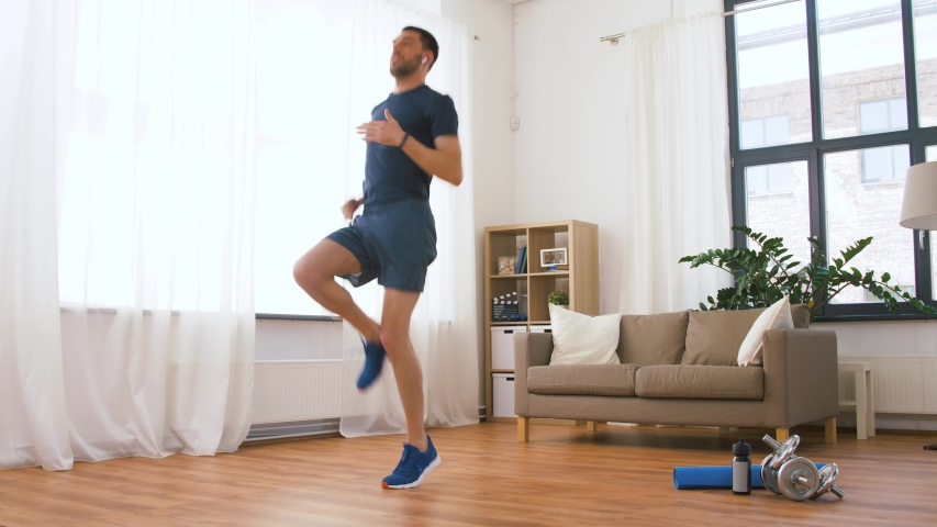 Fitness, sport, technology and healthy lifestyle concept - man with wireless earphones running on spot at home | Shutterstock HD Video #1030360058