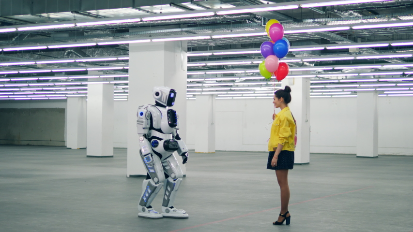 One cyborg receives a bunch of balloons from a woman. | Shutterstock HD Video #1030374428