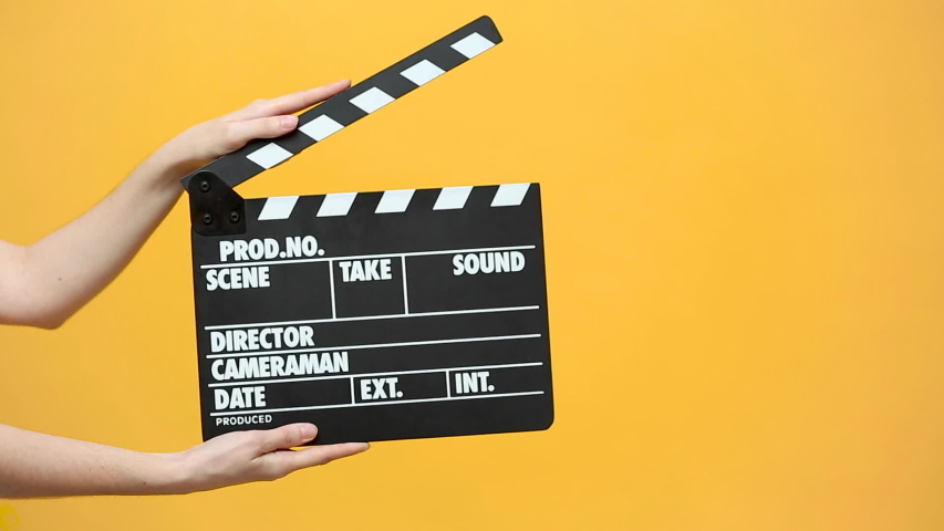 Close up female hold in hand classic director clear empty black film making clapperboard isolated on yellow orange background studio. Cinematography production concept. Copy space advertising mock up. | Shutterstock HD Video #1030421258
