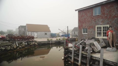 Shoting sideways showing a small city fishing camp during a foggy day, some boats docked, some chalets made of wood - beautiful moddy footage at the coast of Nova Scotia, Canada