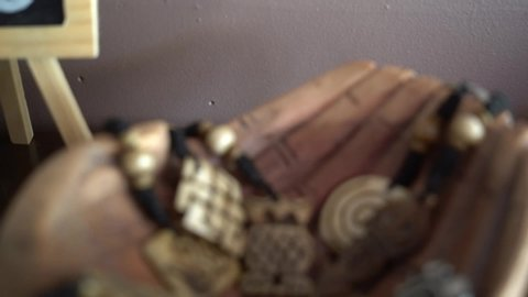 A closer view of the necklace made of wood and nut with OM print is placed on hand shaped-hand,
