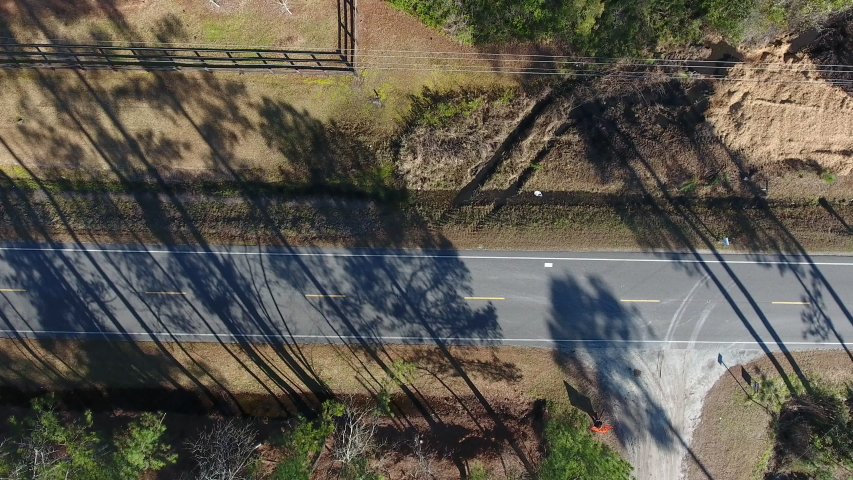 A bird's eye view aerial shot of a back road in North Carolina. Cars drive past tire marks dug into the mud off the side of the road.