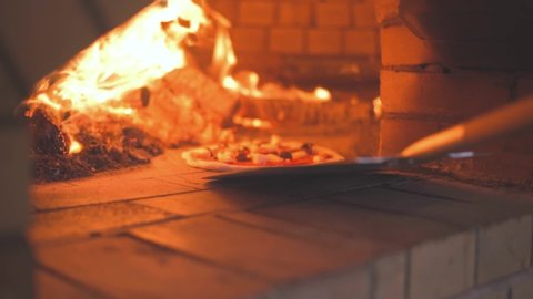 Placing Pizza in Wood fired Pizza Oven using a pizza peel Slow motion shot