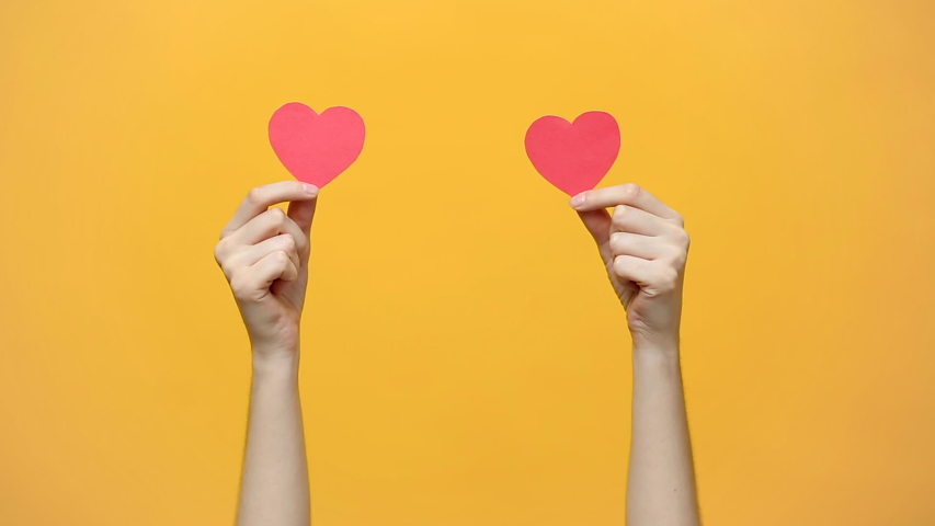 Female blogger hold in hands little red hearts, dancing to music rhythm isolated on yellow orange background. Like blogging blog social network tenderness concept.  | Shutterstock HD Video #1030517558
