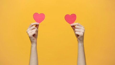Female blogger hold in hands little red hearts, dancing to music rhythm isolated on yellow orange background. Like blogging blog social network tenderness concept.