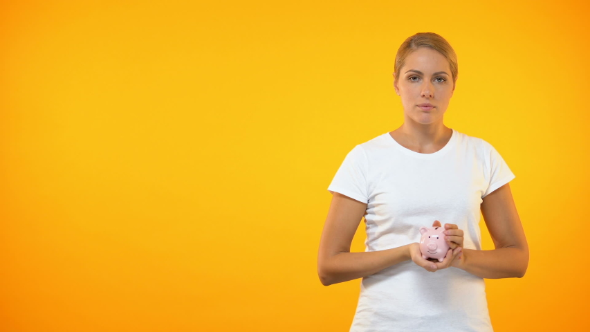 Sad young woman shaking piggybank, lack of money, financial problem, bankruptcy   Shutterstock HD Video #1030538048