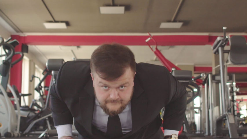A male caucasian businessman in a black suit performs physical exercises in a gym, wring out of the floor and looks into the camera as a concept of a healthy lifestyle office workers #1030540478