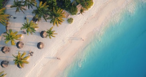 Aerial view of sea waves, umbrellas, palm trees and walking people on sandy beach at sunset. Summer in Zanzibar, Africa. Tropical landscape with parasols, sand, blue water. Top view from drone. Travel