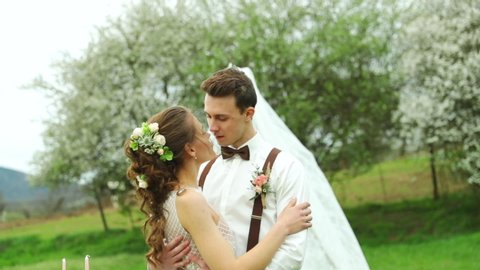 Wedding close us capture of bride and groom kissing in nature in wedding teepee background.