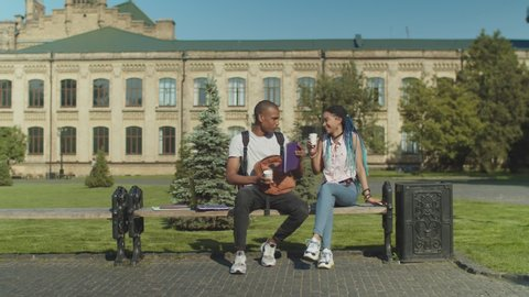 Overworked african american student sleeping at laptop pc outdoors in university park after sleepless night and exhausting study. Mixed race male friend waking up young woman bringing her coffee.