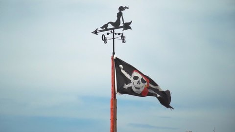 Black Pirate Flag with Skull and Bones Waving In Slow Motion. Compass on Top of The Pole. Blue Background.