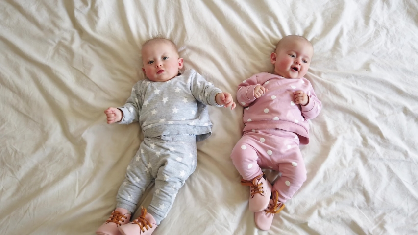 Two girls sisters lie on the bed. Two baby twins on the bed | Shutterstock HD Video #1030682738
