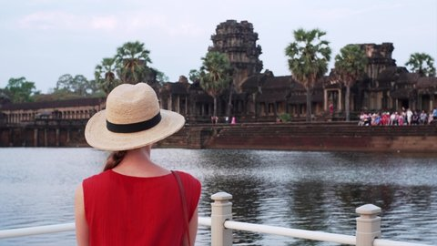 Woman in red dress is taking photo of Angkor Wat temple from bridge. The temple was built in 12th century by khmer civilization and dedicated to Vishnu. Cambodia