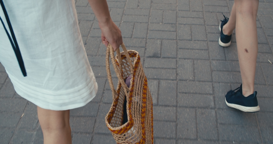 Closeup details of summer female casual street style outfit with bag. Fashionable girl walking at city street. . 4K slow motion raw video footage 60 fps