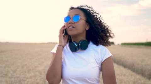 Slow motion follow shot video of beautiful mixed race African American girl teenager young woman in white T-shirt and blue sunglasses walking talking on her mobile cell phone