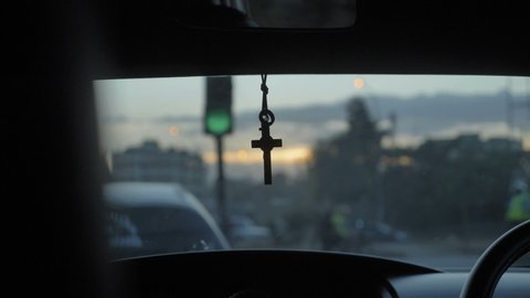 A cross hanging on a mirror of a moving car through the city traffic in the evening