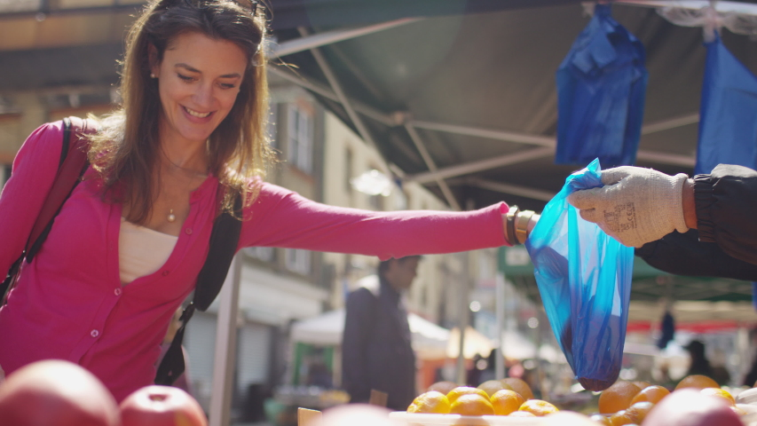 Young female selecting avocados at a fruit and vegetable stall in a street market, in slow motion | Shutterstock HD Video #1030837358