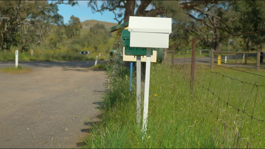 Reveal shot of a long row of mailboxes in rural Australia. | Shutterstock HD Video #1030840328