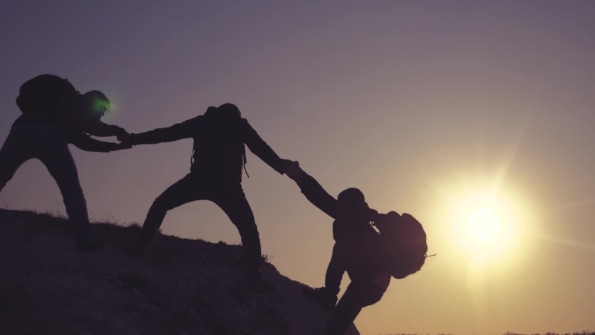 Teamwork help business travel silhouette concept lifestyle . group of tourists lends a helping hand climb the cliffs mountains. people climbers climb to the top overcoming hardships the path to