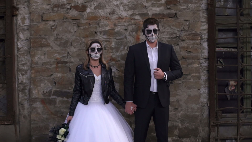 A horrible couple in a wedding dress and costume with makeup in the form of a skeleton stand against an old brick wall in an old abandoned house. The concept of Halloween. Halloween face art. #1030873628