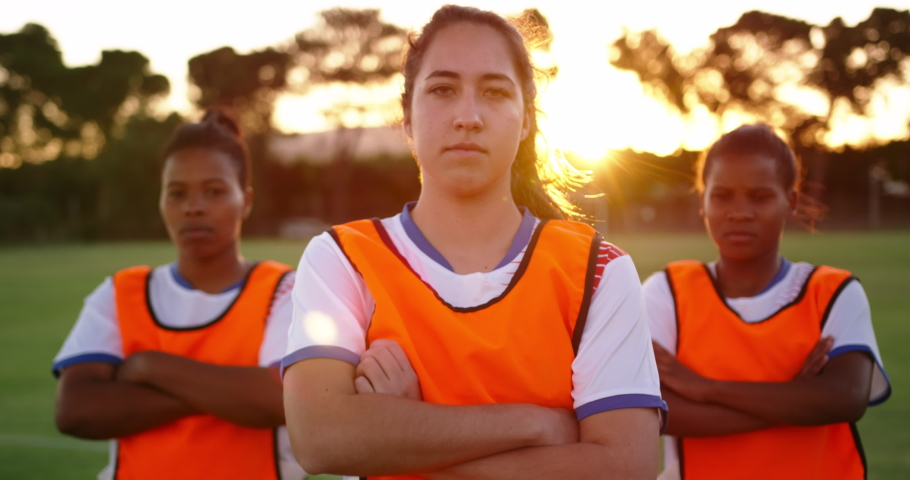 Front view close up of concentrated diverse female soccer team in orange vests standing with arms crossed on soccer field.  | Shutterstock HD Video #1030907048