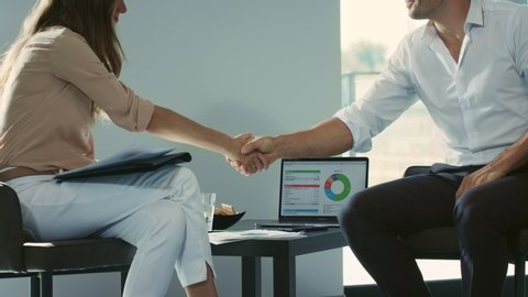 Business people shaking hands after signing documents in luxury house. Closeup handshaking in private house. Professionals shaking hands after agreement.