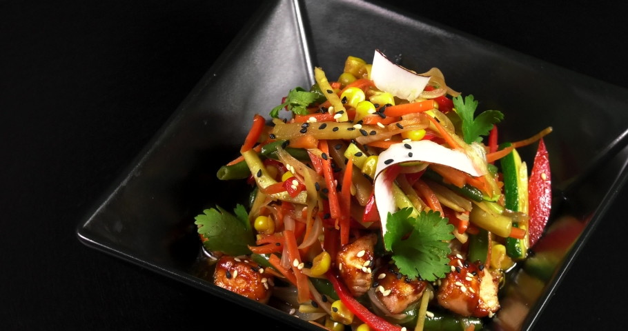 Asian noodles with vegetables and meat on a black background.   Shutterstock HD Video #1030943078