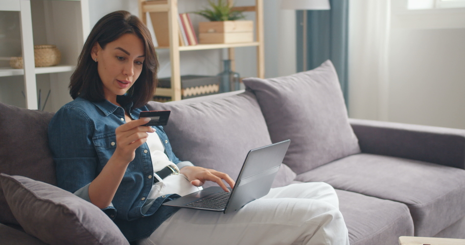 Pretty girl is making online payment holding bank card using modern laptop at home sitting on sofa and smiling. Finance, shopping in internet and youth concept. | Shutterstock HD Video #1030945178