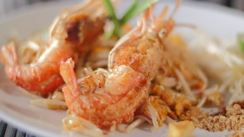 Close up of Crispy crunchy river shrimps on Pad Thai noodle dish. Strong depth of Field and Slow motion.
