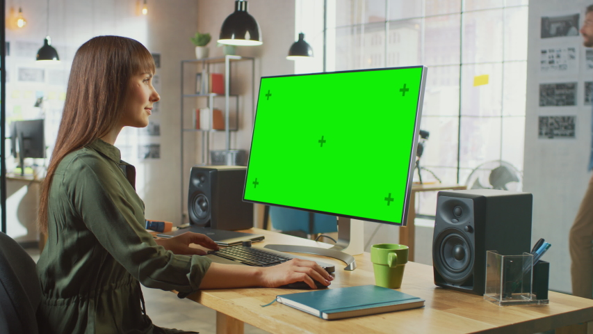 Beautiful Brunette Female Video Editor Works on Her Personal Computer with Big Green Screen Mock Up Display. She Works in a Cool Office Loft. Other Male Creative Colleague Walks in the Background.