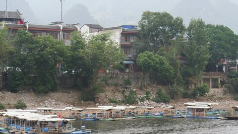 Small Chinese town by river with boats, old houses and karst mountain formations