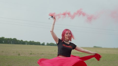 size 40 coupon code half off Close-up of beautiful woman hipster in shorts and long bright skirt  circling holding smoke bomb in countryside. summer wind waving hemline of  female skirt and blowing colorful smoke over field.