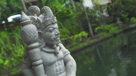 Indonesia god statue in front Bali temple, Indonesia. Traditional indonesian hindu symbol. Ancient sculpture religious idol. Balinese spiritual architecture. Asian culture. Tourism and travel concept