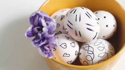 Yellow cup on a white background with Easter eggs. easter eggs in a yellow cup. white eggs with black pattern. beautiful filet flower on Easter eggs.