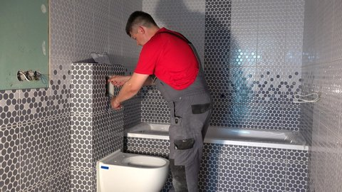 Plumber man draw water from pipe of toilet flushing mechanism. Worker install toilet flush button in new modern bathroom. Static shot.