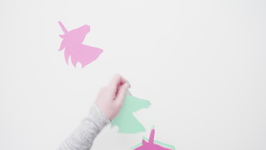 Flat lay. Colorful unicorn paper cutouts on a white background. | Shutterstock HD Video #1031033738