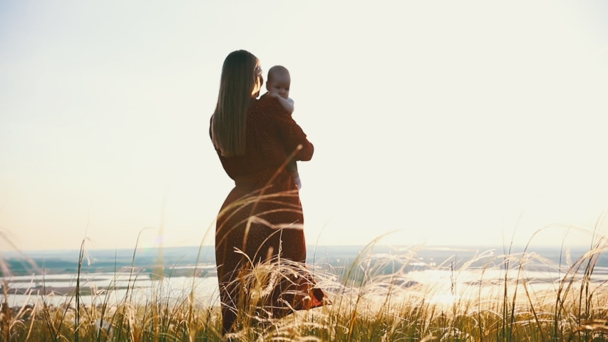 A woman holds a child in her arms. Against the backdrop of the sunset. | Shutterstock HD Video #1031066108