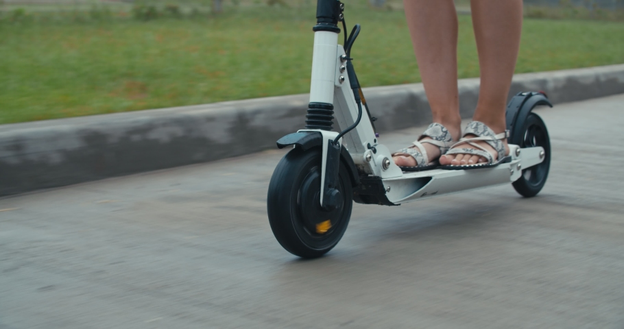 Rainy day, wet road. Close-up of legs of woman standing on the electric kick scooter from home to work or study. 4K slow motion raw video footage 60 fps | Shutterstock HD Video #1031089628