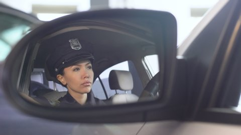 Confident policewoman putting on sunglasses looking into rearview mirror of car