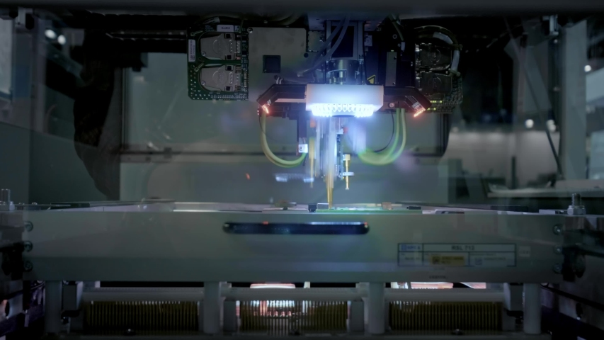 Factory Machine at Work: Printed Circuit Board Being Assembled with Automated Robotic Arm, Surface Mounted Technology Connecting Microchips to the Motherboard. Time Lapse Macro Close-up Footage. | Shutterstock HD Video #1031115848