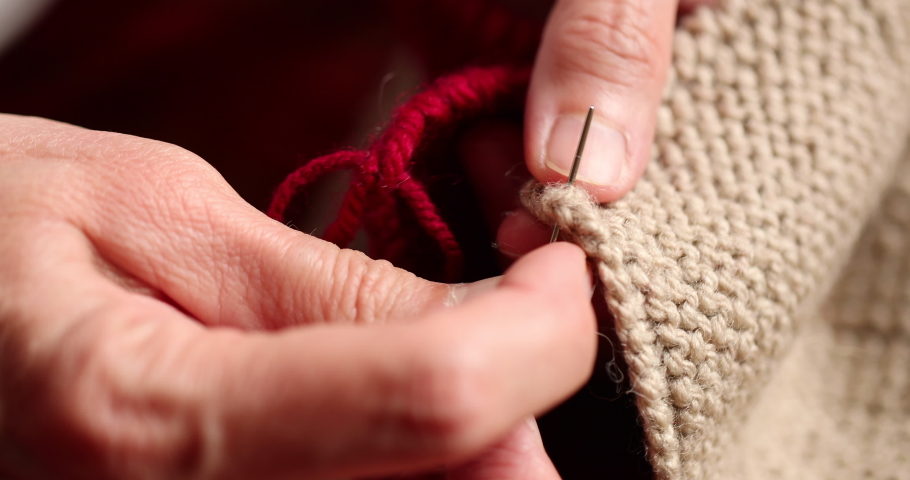 Close-Up of woman hands knitting red and beige wool. 4K Resolution | Shutterstock HD Video #1031154638