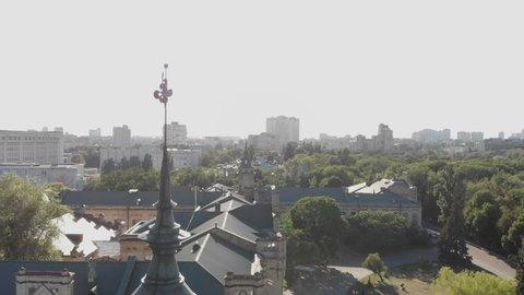 Aerial of a beautiful historic building with a thin spire and a weathercock in Kyiv in summer.