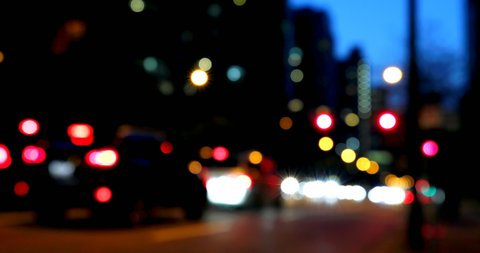 Front view of colorful bokeh of car lights on the street at night. Vehicles are halt at traffic signal