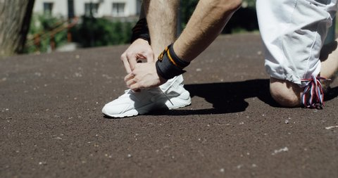 Workout, the athlete laced up the laces white sneakers, view of the legs.