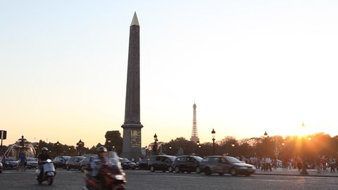 Paris, France - April 5, 2019: Place de la Concorde with Egyptian obelisk and Eiffel tower in background and car traffic during sunny summer afternoon with blue sky. Wide Shot.