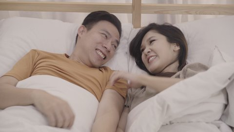 Asian couple lying on bed in bedroom, couple feeling happy having funny time playing under blanket together on bed at home. Couple relax enjoy love moment at home concept.